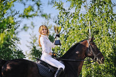 Winners - young girl and bay horse. With cup stock image