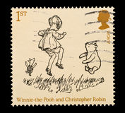 Winnie The Pooh. Commemorative mail stamp printed in the UK featuring the well known A.A. Milne's fictional charachters of Winnie The Pooh, Christopher Robin and Royalty Free Stock Images