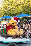 Winnie the Pooh rides a sleigh in Disneyland Parade. Winnie the Pooh rides a sleigh in Disneyland's A Christmas Fantasy Parade.  He wears a red Christmas hat and Stock Image