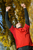 Winning athlete. Happy male athlete raising arms celebrating victory. Winner sportsman outdoors Stock Images