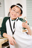 Winning boy with his medal and trophy. An asian boy showing his winning sport medal and trophy Royalty Free Stock Photos