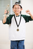 Winning boy with his medal and trophy. An asian boy excited aboyt his winning sport medal and trophy Royalty Free Stock Photos