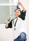 Winning boy with his medal and trophy. An asian boy excited aboyt his winning sport medal and trophy Stock Photos