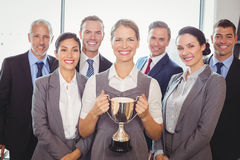 Winning business team with an executive holding trophy Royalty Free Stock Photo