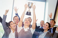 Winning business team with an executive holding trophy Royalty Free Stock Photos