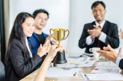 Winning business team gold trophy , business team happy consent and successful business team rewarded. For in the office royalty free stock photos