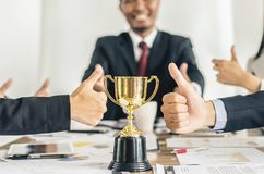 Winning business team gold trophy , business team happy. Consent and successful business team rewarded for in the office royalty free stock images