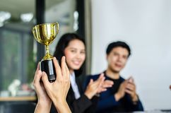 Winning business team gold trophy , business team happy. Consent and successful business team rewarded for in the office royalty free stock photography
