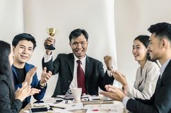 Winning business team with a man executive holding a gold trophy Stock Images