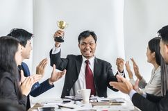 Winning business team with a man executive holding a gold trophy. Stock Photo