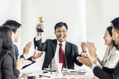Winning business team with a man executive holding a gold trophy . Winning business team with a men executive holding a gold trophy . happy and successful stock photography