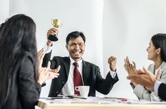 Winning business team with a man executive holding a gold trophy. Winning business team with a men executive holding a gold trophy . happy and successful stock photography