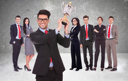 Businssteam rewarded for it's work with trophy. Winning business team with a young men executive holding a gold trophy . happy and successful businssteam Royalty Free Stock Image