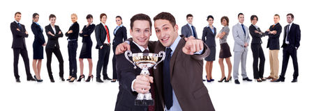 Winning businessteam. With two leaders, one holding a trophy, one pointing to you Stock Photos