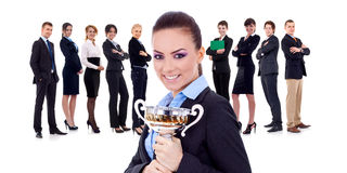 Winning businessteam, female holding trophy. Winning businessteam with female executive holding a gold trophy Royalty Free Stock Photos