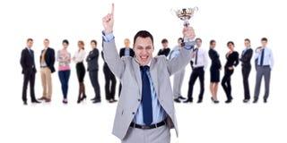 Winning businessteam leader holding trophy. Winning businessteam with male executive holding a gold trophy Stock Photo