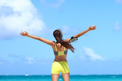 Winning carefree fitness woman expressing happiness on beach summer vacation. Winning carefree woman runner expressing happiness on beach summer vacation. Back stock photo