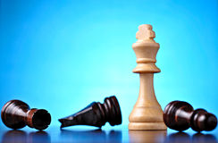Winning in chess. With a white wooden king standing upright over vanquished fallen pawns against a blue background with highlight and copyspace Stock Image