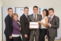 Winning corporate business team. Group people dressed according to business dress code keep awarding certificate with WINNER sign stock photo