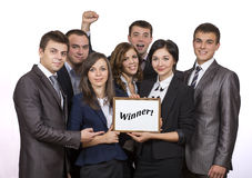 Winning corporate business team. Group people dressed according to business dress code keep awarding certificate with WINNER sign royalty free stock photography