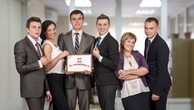 Winning corporate business team. Six people dressed according to business dress code keep awarding certificate with We are the champions sign stock images