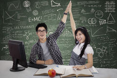 Winning Couple. Happy student couple winning with computer on the desk Royalty Free Stock Image