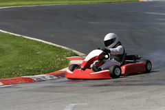Winning the curve. Go-Kart driver successfully passing the curve Royalty Free Stock Photography