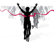 Winning Cyclist crosses the finish line in a race Royalty Free Stock Photos