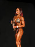 Winning Figure Gal Displays Trophy royalty free stock photos