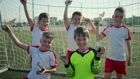 Winning football team of little boys is demonstrating rewards on stadium