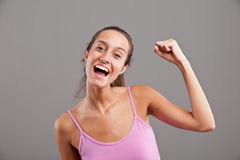 Winning girl raising up her arm happily Royalty Free Stock Image