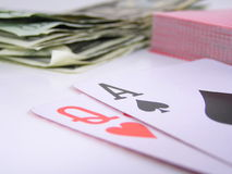 Winning hand. Blackjack with a queen of hearts and ace of spades. pile of money and cards out of focus in the background stock photo