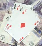 Winning Hand. A winning poker hand displayed ontop of a pile of cash Stock Photo