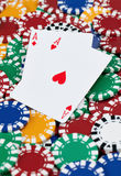 The Winning Hand. A pair of red aces set on top a large pile of poker chips. aces set on top a large pile of poker chips Royalty Free Stock Photos