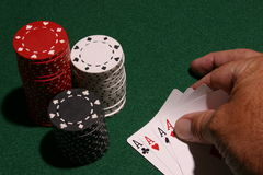 The Winning Hand. Close up of a hand placing four acres on a green table top with stacks of poker chips near by Royalty Free Stock Image