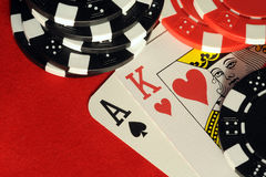 Black jack. A winning hand of cards on a red felt background with stacks of chips Royalty Free Stock Images