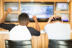 Winning and losing. Closeup portrait, two men watching a sports game on tv. One guy rejoices, other guy feels terrible. Team spirit concept royalty free stock image