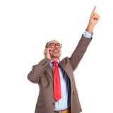 Winning old businessman talking on the phone pointing up Stock Image