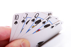 Winning poker hand. Royal flush in spades - held in left hand and raised slightly off table. White background stock photo