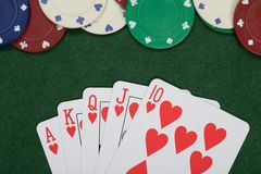 Winning poker hand and casino chips. Displayed on green baize with fanned cards showing a straight royal flush viewed from above in a lucky gambling concept Royalty Free Stock Images