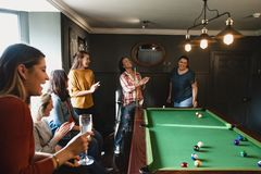 Winning at Pool. Small group of friends playing pool in a games room in a house stock photos