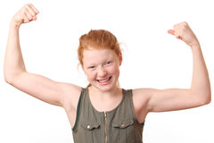 Winning. Portrait of a winning young girl flexing muscles on white background royalty free stock photos