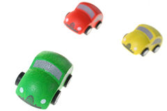 Winning race. Cars racing to win, green car ahead of the rest. wooden toy cars in red green and yellow, isolated on white. Metaphor for race, success, winning royalty free stock image