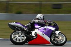 Winning Race. Purple bike dashing on the track Royalty Free Stock Image