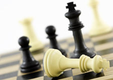 Winning Strategy. Chess Pieces on a board, depicting check mate. (Fallen King). The shot can be a business metaphor relating to a winning strategy. Main focus is Royalty Free Stock Photo