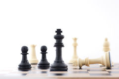 Winning Strategy. Chess Pieces on a board showing the King. The shot can be a business metaphor relating to a winning strategy or leadership. Main focus is on royalty free stock photo
