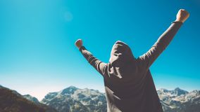 Winning and success. Victorious female person on mountain top. Winning and success. Victorious female person standing on mountain top with arms raised in V Stock Image