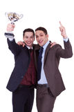 Winning team. Two business men winning a trophy on white background Stock Image