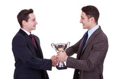 Winning team. Business men handing a trophy to his winning coleague and handshake him Stock Photography