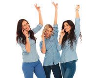 Winning team of casual women talking on the phone. Standing with hands in the air and making the victory sign Royalty Free Stock Photos